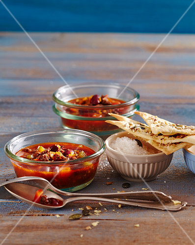 Spicy midnight soup with minced meat and beans served with crackers with various seeds and cheese