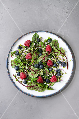 Green vegan salad with berries strawberry, blueberry, sprouts, young beetroot leaves on ceramic plate