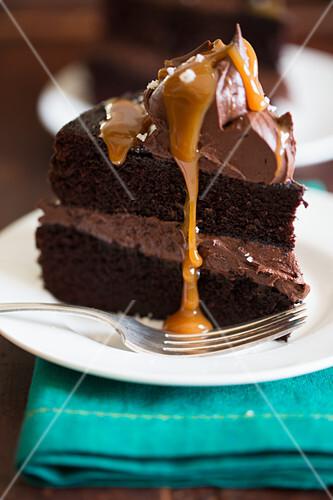 A slice of chocolate cake with caramel sauce