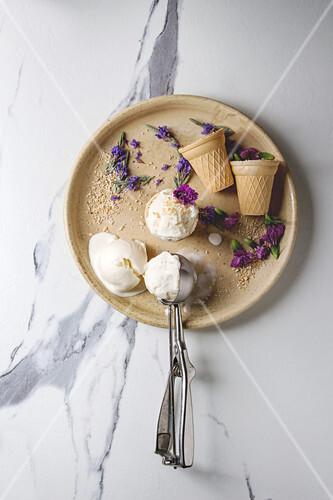Homemade vanilla ice cream balls served with purple edible flowers