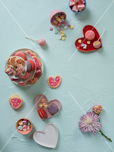 A colorful array of valentines sweets layed out on a mint green surface