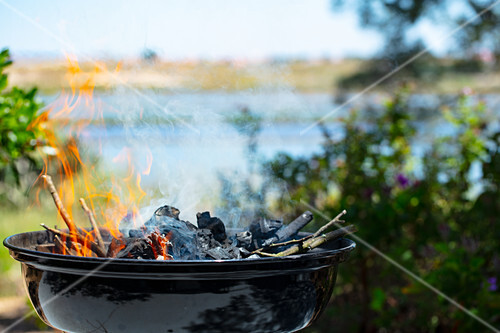 A charcoal barbecue in front of a river