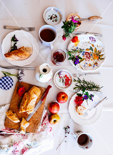 A table with a white cloth with French bread, marmelade, apples and tea