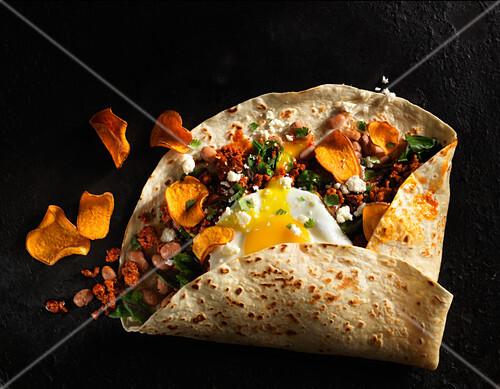 Burrito with chard, pinto beans, chorizo, fried egg, and sweet potato chips