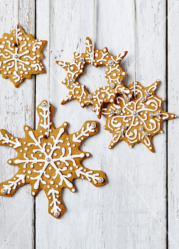 Winter star cookies hanging from a string in front of a white wood wall