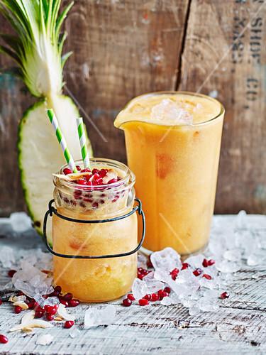Tropischer Fruchtsaft mit Ananas, Papaya, Mango und Granatapfel