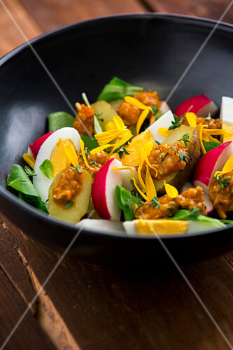New potatoes with egg, radishes, lamb's lettuce, pesto and marigold flowers