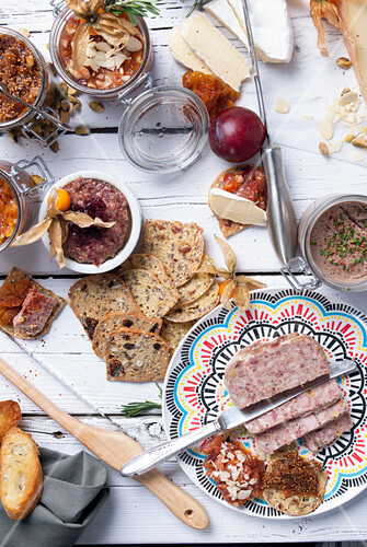 Various pâtés, cheese and bread on a white wooden table