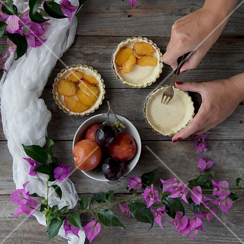 Plum tartlets being made, pastry bases being pierced with a fork