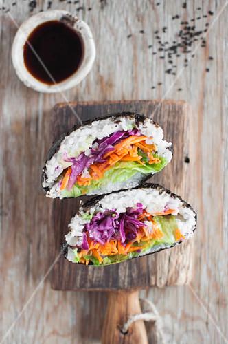 Onigirazu (Japanese sushi sandwich) - seaweed (nori), sushi rice, pickles vegetable, avocado and wasabi