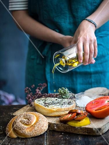 Ein Sesambrötchen vor dem Belegen mit Olivenöl beträufeln