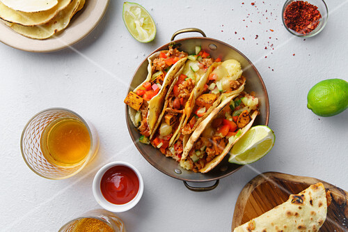 Overhead image of mexican tacos with chili con carne and grated cheese