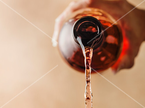 Detail image of rose wine being poured out of the bottle