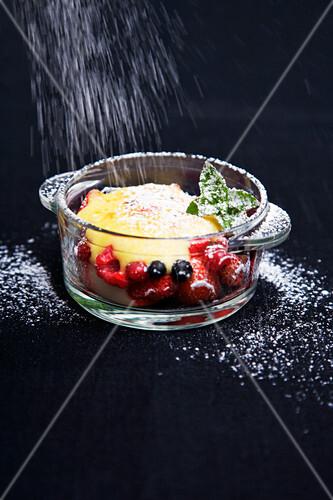 Gratin mit Beeren und Pfirsichen wird mit Puderzucker bestäubt