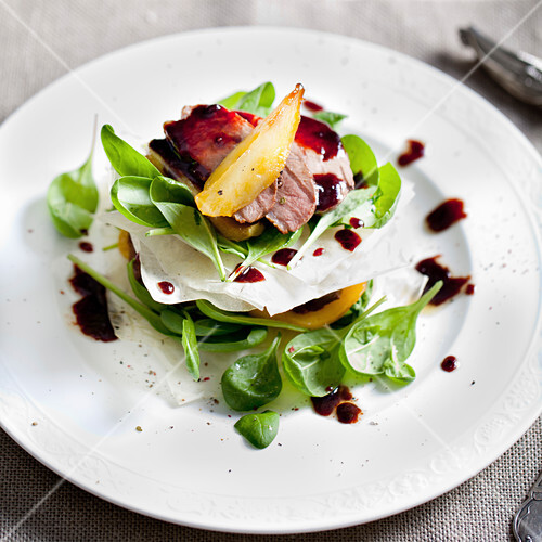 Duck breast roasted with pear, salad on a white plate
