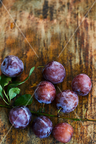 Fresh plums on a wooden surface