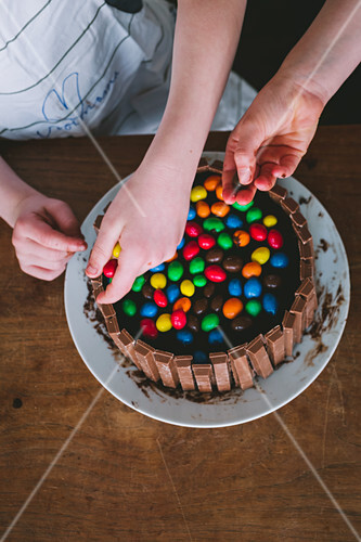 Children hands decorating a cake with colored candy