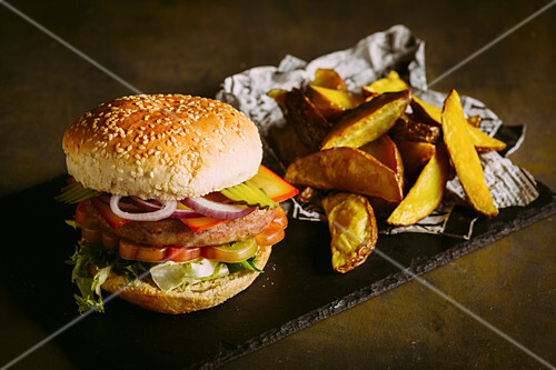 Gourmet burger with chicken meat, cheese, tomato, lettuce and onion with fries