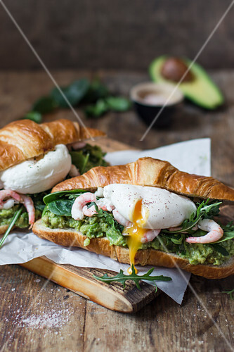 Croissant with avocado puree, shrimps, poached egg, rocket and spinach, salt in a bowl, avocado, spinach leaves