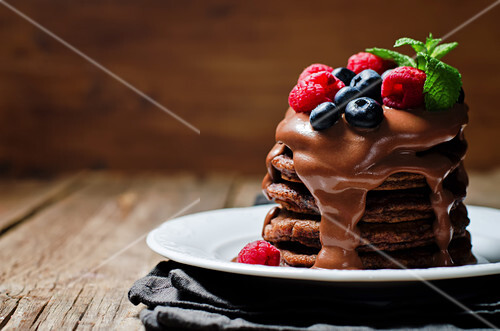 Chocolate pancake with blueberries, raspberies and chocolate sauce