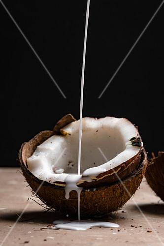 Kokosmilch fliesst in Kokosnusshälfte