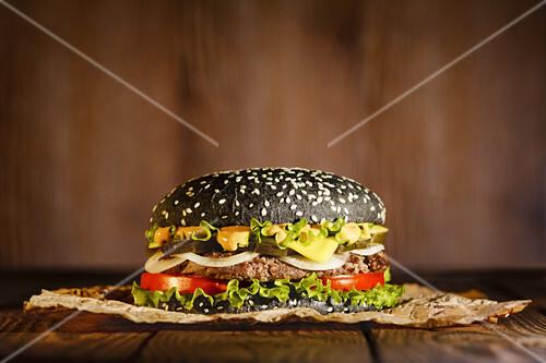 Black burger on paper on a dark background