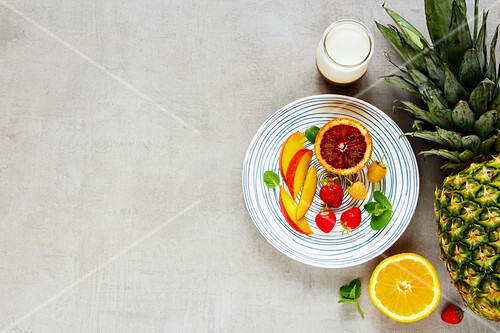 Delicious breakfast with fresh fruit and berries, greek yogurt on light table background