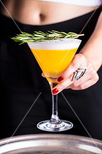 A cocktail with an egg white topping and rosemary being served