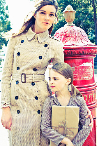 A young woman wearing a beige coat and a little girl with a package standing next to an old-fashioned British postbox