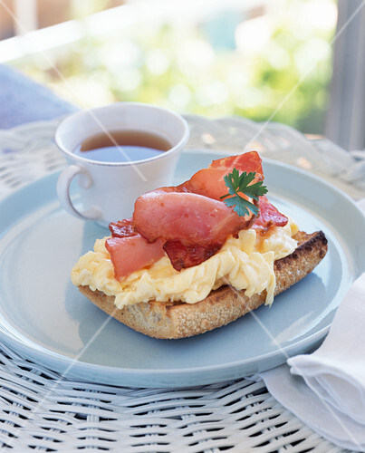 Scrambled egg and bacon on toasted sourdough baguette slice