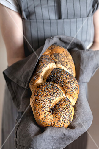 Girl in an apron holding a challah with poppy seeds on a linen napkin