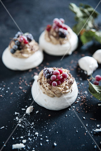 Vegan pavlova made with aquafaba, topped with coffee butter cream and frozen berries