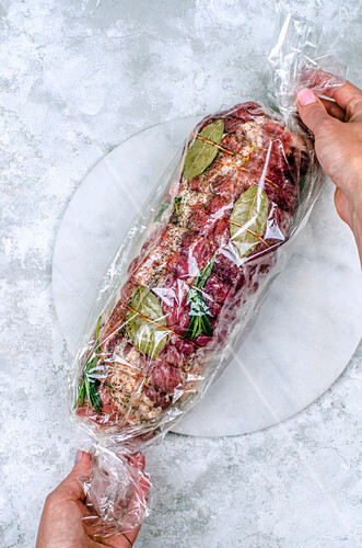 Meatloaf in the sleeve before baking in the hands of the girls