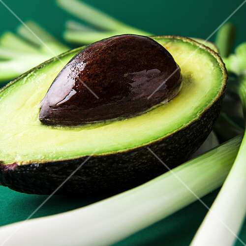 An avocado, halved, with stone