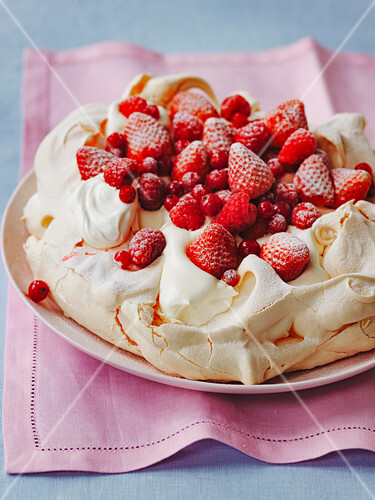 Strawberry and redcurrant pavlova with whipped cream and meringue base