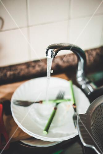Wasser fließt über schmutzigem Geschirr