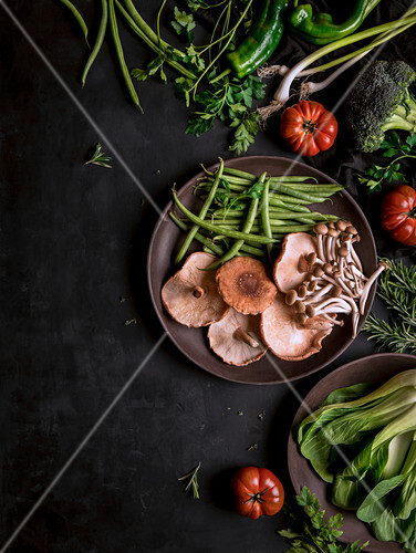 Composed wooden bowls with various healthy green and mushroom on black table