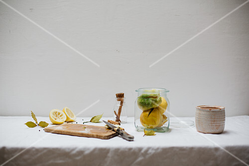 Ingredients for salted lemons (cinnamon, salt, bay leaves, peppercorns) on a light linen cloth