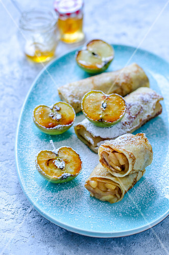 Thin pancakes stuffed with apple and a jar of honey on blue plate