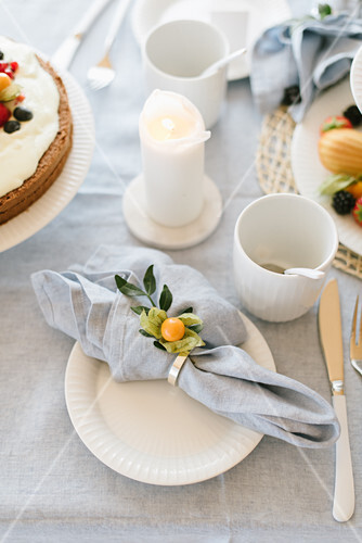 Place setting with linen napkin and cape gooseberry on table set for afternoon coffee