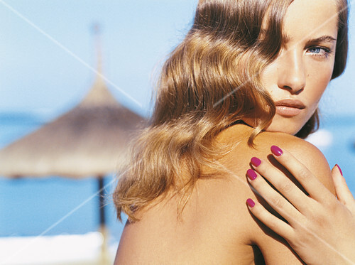 A young blonde woman with varnished fingernails