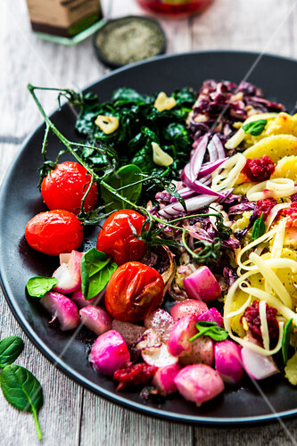 A breakfast bowl with potatoes, spinach, tomatoes, radishes and cheese