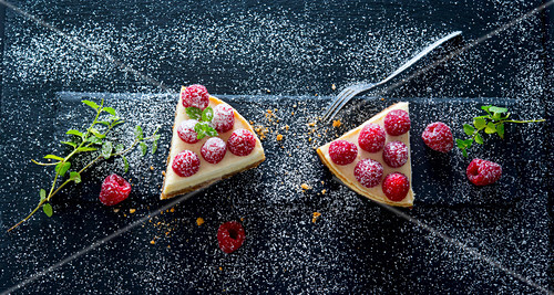 A slice of cheesecake with raspberries