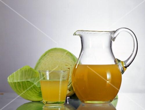Sauerkraut juice in glass & carafe & half a white cabbage