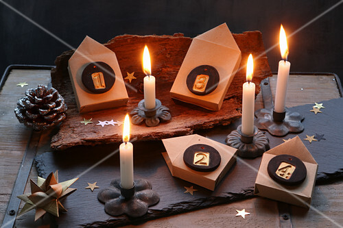 Advent arrangement of numbered paper houses on tree bark and slate board with lit candles