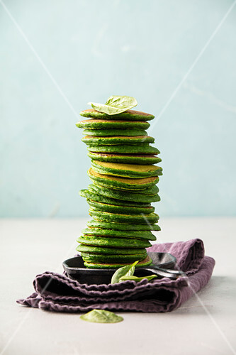 Spinach pancakes stack on blue background