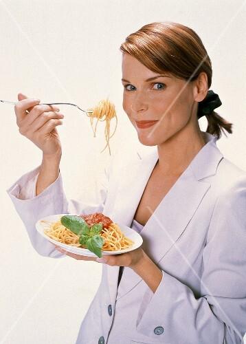 Woman Eating Spaghetti with Tomato Sauce