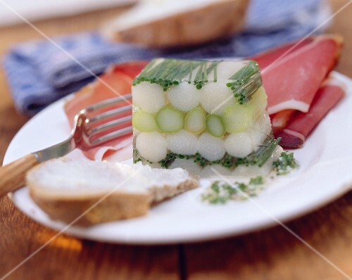 White & green asparagus jelly with ham on a plate