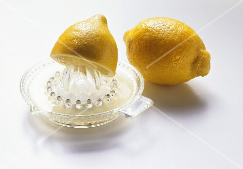 Lemon half on lemon squeezer, with whole lemon behind