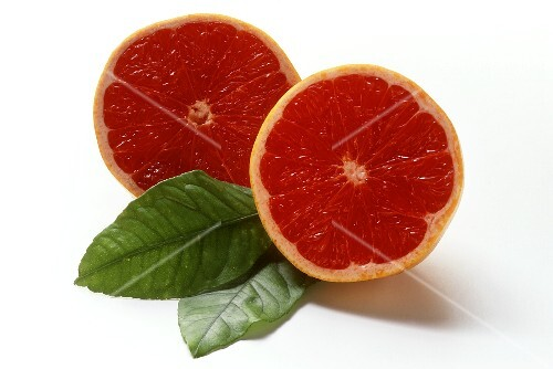 Halved pink grapefruit and two leaves
